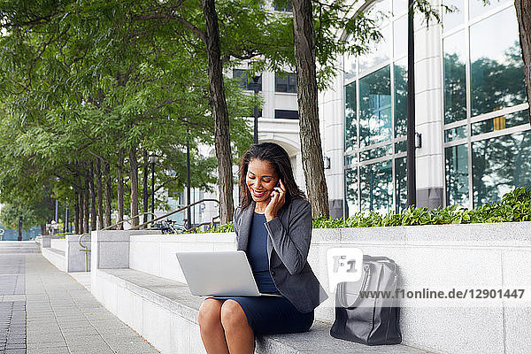 Geschäftsfrau benutzt Handy und Laptop auf Straßenplätzen