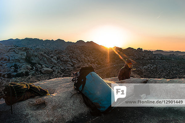 Rock climber on summit at sunset  Joshua Tree  California  USA