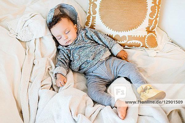 Kleiner Junge mit Kapuze schläft auf Decke