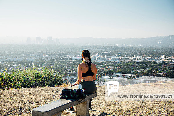 Woman sitting on bench on hilltop  Los Angeles  US
