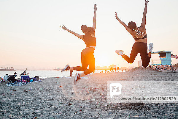 Friends jumping on beach  Long Beach  California  US