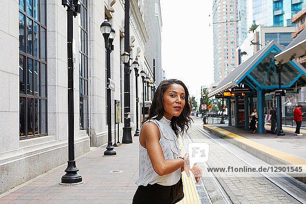 Geschäftsfrau kontrolliert Zeit bei Stadtbahnlinie