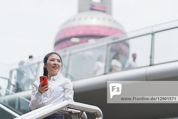 Junge Geschäftsfrau mit Smartphone auf der Stadttreppe  Shanghai  China