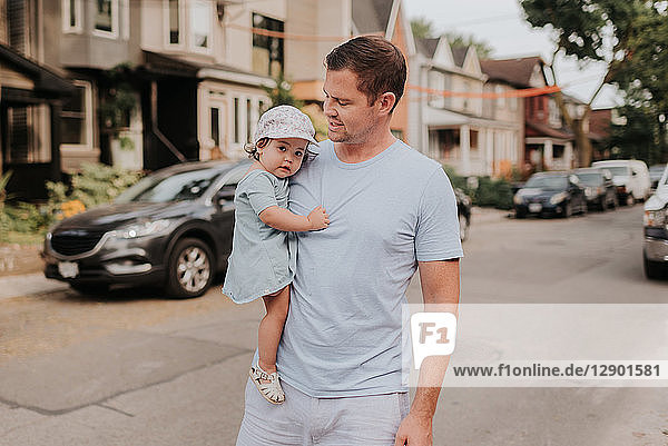 Man carrying daughter on street