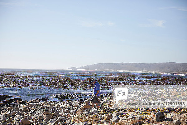 Tourist betrachtet Steinhaufen am Strand  Kapstadt  Westkap  Südafrika