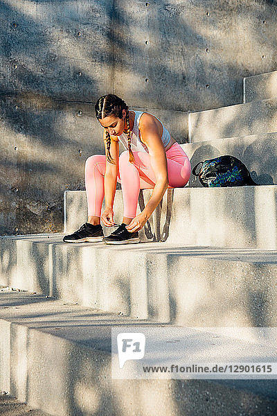 Woman tying trainer laces on steps