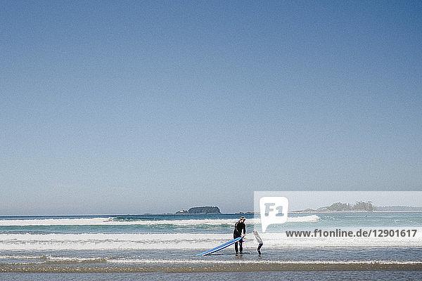 Vater und Kind beim Surfen am Strand  Tofino  Kanada