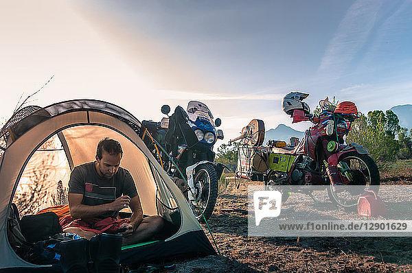 Biker using mobile phone inside tent  Fresno  California  USA