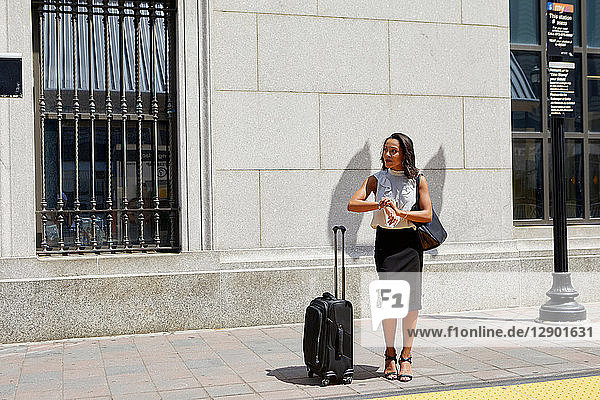 Geschäftsfrau kontrolliert Zeit am Bordstein