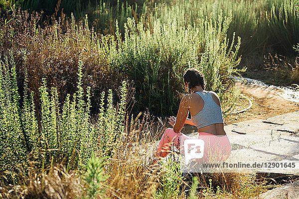 Woman relaxing among shrubs