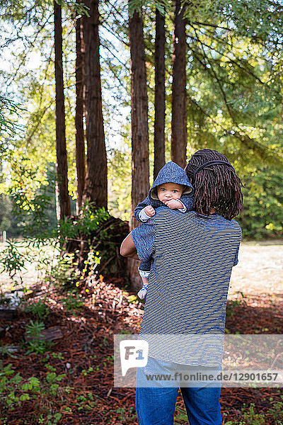 Mature man carrying baby son in forest  portrait