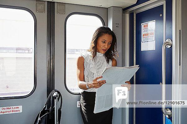 Geschäftsfrau liest Zeitungen im Zug