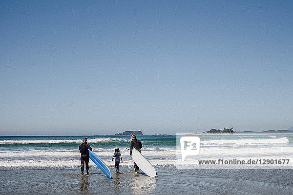 Friends with daughter surfing on beach  Tofino  Canada