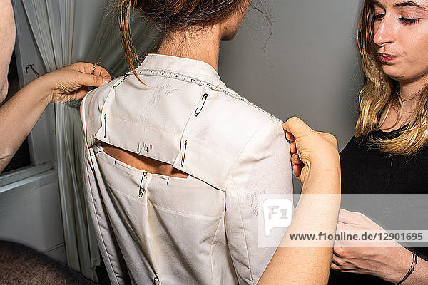 Fit model in fitting of tailored jackets before fashion show
