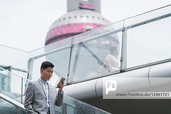 Junger Geschäftsmann betrachtet Smartphone auf Stadttreppe  Shanghai  China