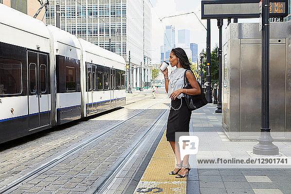 Businesswoman waiting on light rail platform