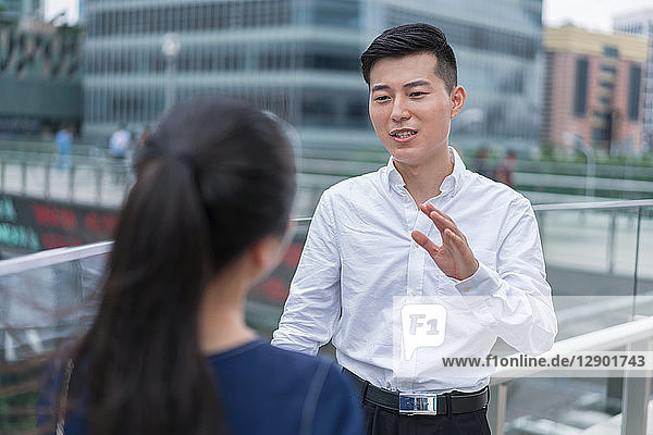 Young businesswoman and man talking on balcony in city financial district  Shanghai  China