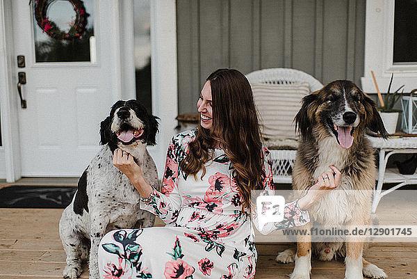 Frau und ihre zwei Hunde sitzen auf der Veranda