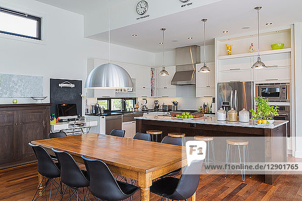 Open plan kitchen dining area with antique table  marble top kitchen island in luxurious modern cube style house interior
