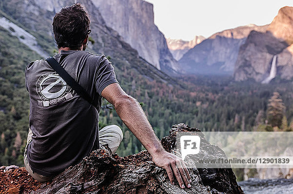 Rock climber looking out at mountain ranges  Yosemite National Park  California  USA