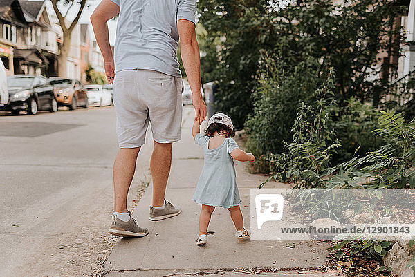 Man with toddler daughter on street