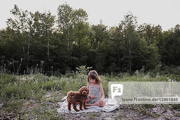 Mädchen und Welpe auf Picknickdecke