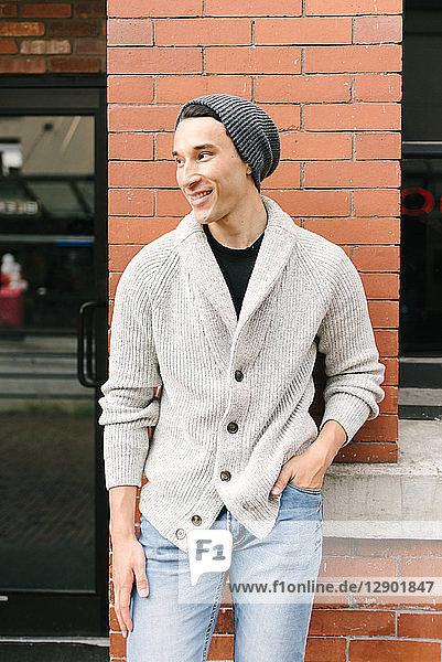 An Ziegelmauer gelehnter junger Mann  Vancouver  Kanada