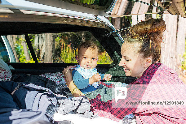 Mid adult woman with baby son sitting up in car boot
