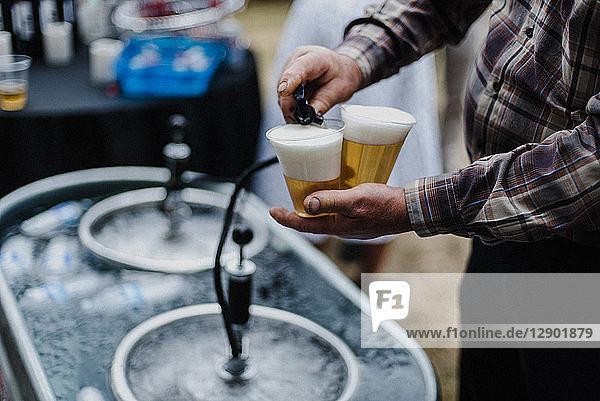 Mann gießt Bier aus Fässern im Kühlbad beim Grillen  abgeschnitten