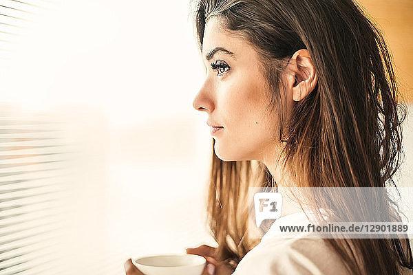 Frau mit Becher beim Betrachten am Fenster