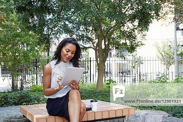 Geschäftsfrau benutzt digitales Tablet im Park