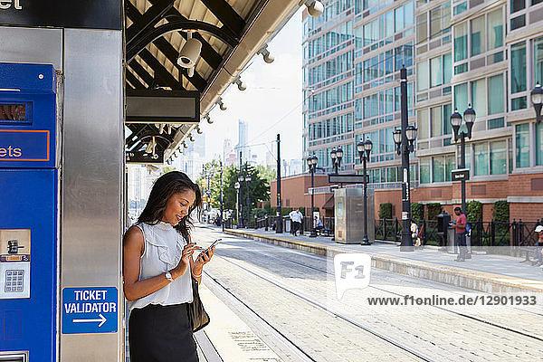 Geschäftsfrau benutzt Handy am Fahrkartenautomaten