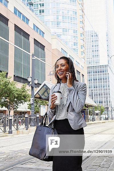 Geschäftsfrau benutzt Mobiltelefon auf der Straße