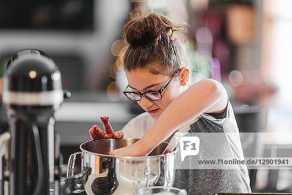 Mädchen legt Zutaten in Rührschüssel für Weihnachtsplätzchen an der Küchentheke