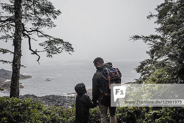 Vater und Kind schauen aufs Meer hinaus  Tofino  Kanada
