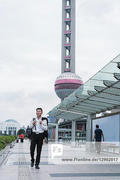 Junger Geschäftsmann schlendert durch die Stadt  Shanghai  China