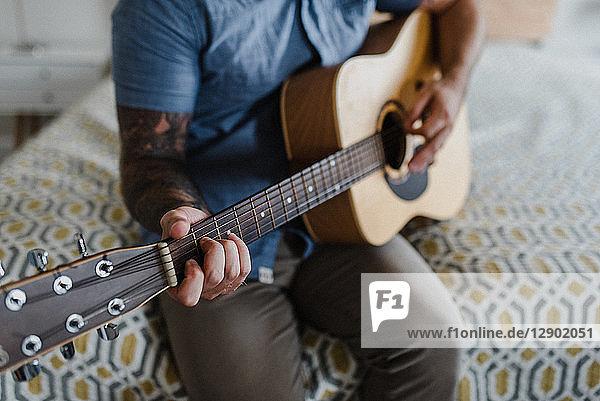 Gitarrist spielt Musik auf dem Bett
