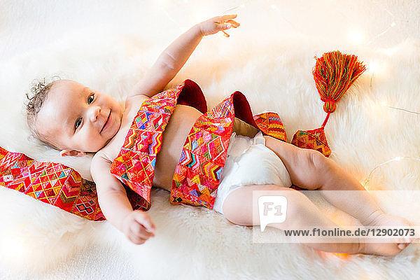 In buntes Textil gewickelter Junge liegt auf pelzigem Teppich
