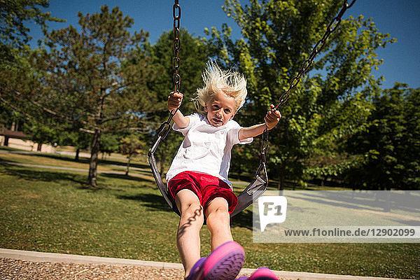 Boy on swing in park