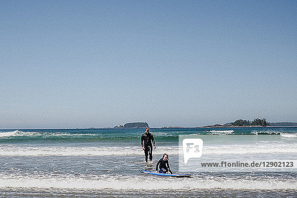 Father and daughter surfing on beach  Tofino  Canada