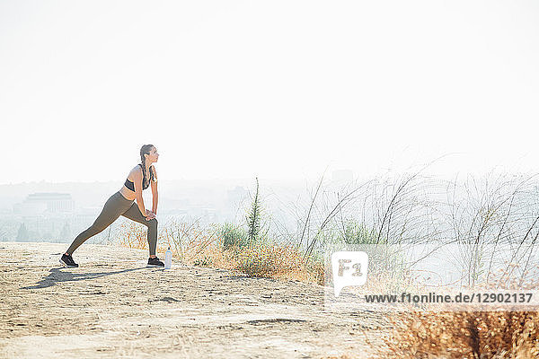 Woman doing stretching exercise on hilltop