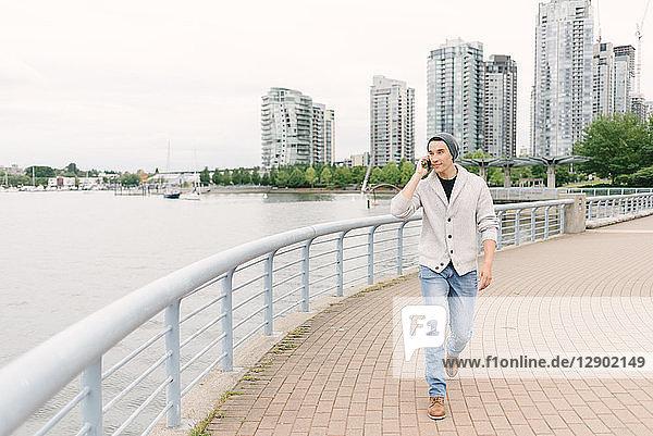 Junger Mann telefoniert beim Spaziergang am Deich entlang  Yaletown  Vancouver  Kanada