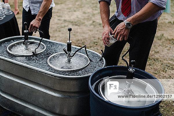 Männer  die beim Grillen Bier aus Fässern im Kühlbad ausschenken  abgeschnitten