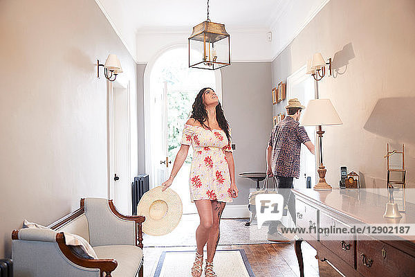 Woman looking up at hotel lobby lampshade  boyfriend carrying suitcase