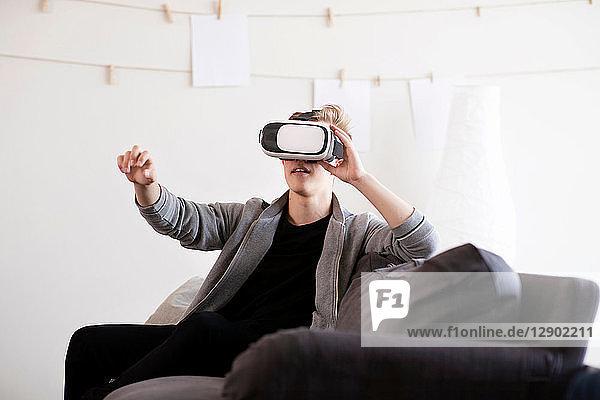 Teenager-Junge auf dem Sofa  der durch ein Virtual-Reality-Headset schaut und die Hand ausstreckt
