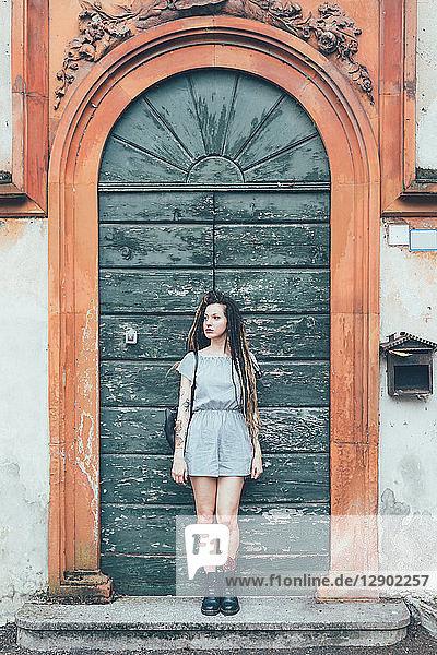 An gewölbte Tür gelehnte Frau