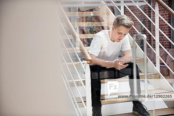 High-School-Junge sitzt auf der Schultreppe und schaut auf ein Smartphone