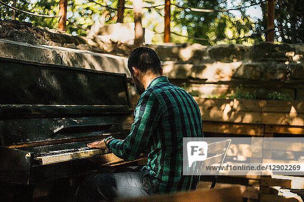 Mann spielt Klavier im Park