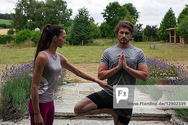 Yogalehrerin  die einem jungen Mann Yoga im Garten beibringt  Baumstellung
