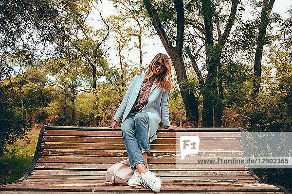 Stilvolle Frau mit langen blonden Haaren auf Parkbank sitzend  Ganzkörperporträt